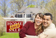 Happy Couple in Front of Sold Home For Sale Real Estate Sign and House.